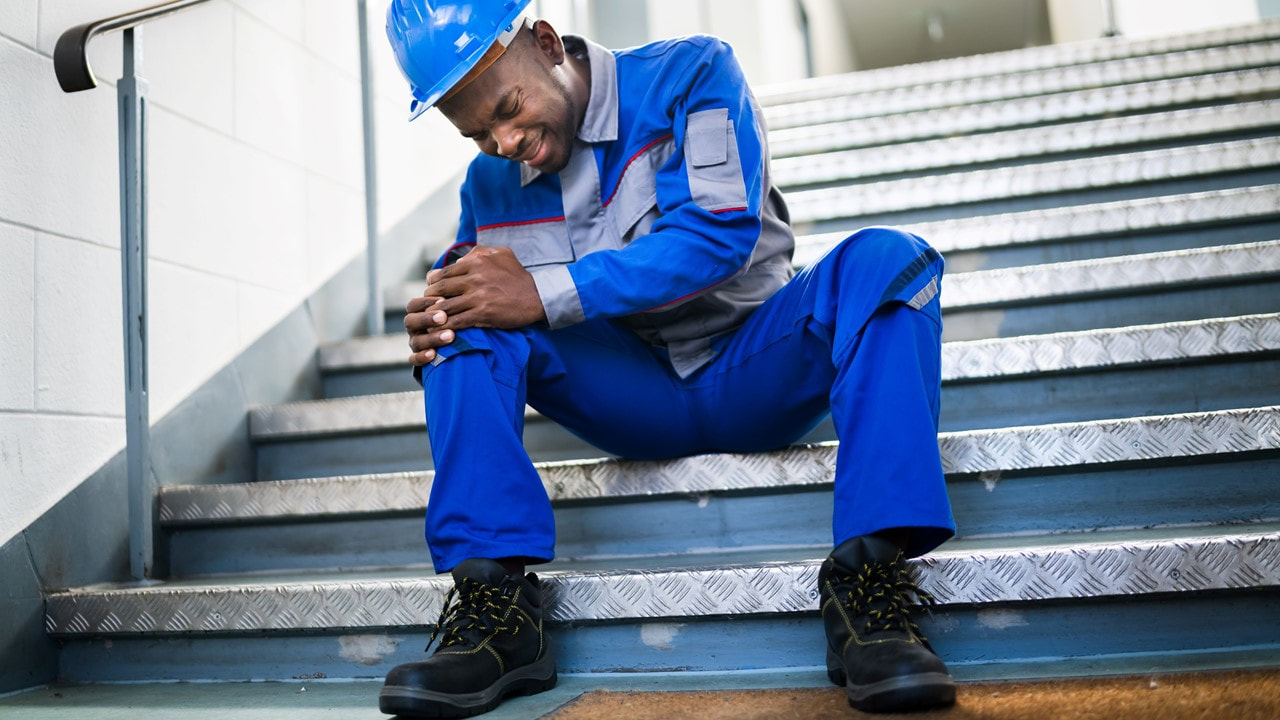 Picture of a male commercial worker holding his knee after a slip and fall on metal stair